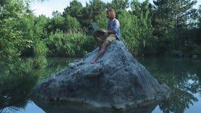 Een jonge freelance kerel zit op een steen in het midden van een meer met laptop Freelance concept Het werk aangaande reis draadl stock videobeelden