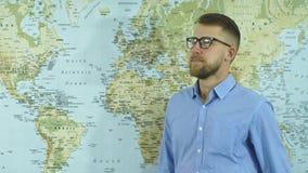 Een jonge gebaarde mens in glazen bekijkt de wereldkaart en het maken van plannen stock videobeelden