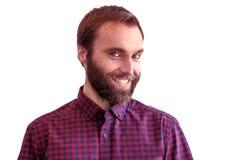 Een jonge gebaarde mens met een sluwe vriendschappelijke glimlach op witte backgroun Royalty-vrije Stock Fotografie