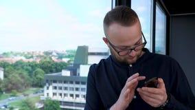 Een jonge, gebaarde mens met glazen blijft dichtbij het venster Hij kijkt aan zijn mobiele telefoon en typt bericht stock video
