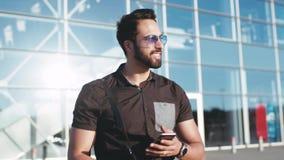 Een jonge gebaarde sterke mens in zonnebril die de luchthaven weggaan en zijn telefoon met behulp van die, graag aan het glimlach stock footage