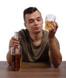 Een jonge gedronken die mens op een witte achtergrond wordt geïsoleerd Alcoholisch met een fles van whiskyzitting bij de lijst De stock foto's