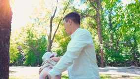Een jonge gelukkige vader houdt een kleine dochter met zijn handen en verdraait haar rond hem die in een de zomerpark, met a spel stock footage