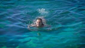 Een jonge gelukkige vrouw die in azuurblauwe overzees zwemmen stock footage