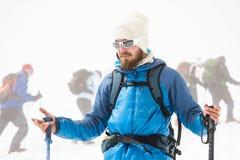Een jonge gids met een baard verklaart de groep aan de achtergrond van een andere stijgende groep klimmers Stock Foto's