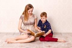 Een jonge glimlachende moeder en een zeven-jaar-oude zoon letten op een fotoalbum samen, zittend op het tapijt in de ruimte stock foto