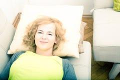 Een jonge glimlachende vrouw die op de bank ontspannen stock foto's