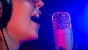 Een jonge glimlachende vrouw in glazen die in T.L.-verlichting in de studio zingen royalty-vrije stock afbeeldingen