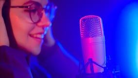 Een jonge glimlachende vrouw in glazen die in T.L.-verlichting door de microfoon zingen royalty-vrije stock foto's