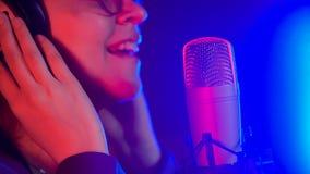 Een jonge glimlachende vrouw in glazen die in T.L.-verlichting zingen stock fotografie