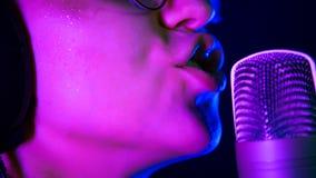 Een jonge glimlachende vrouw in hoofdtelefoons die in T.L.-verlichting in de studio zingen stock afbeeldingen