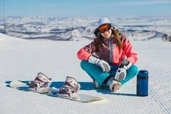 Een jonge glimlachende vrouw zit op een berghelling met een snowboard en een thermosfles stock foto's