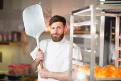 Een jonge grappige bakker met een pizzaspatel in zijn handen tegen de achtergrond van een oven stock fotografie