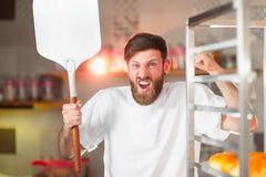 Een jonge grappige bakker met een pizzaspatel in zijn handen tegen de achtergrond van een oven stock foto's