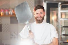 Een jonge grappige bakker met een pizzaspatel in zijn handen tegen de achtergrond van een oven royalty-vrije stock fotografie