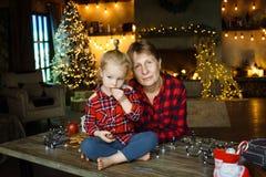 Een jonge grootmoeder met haar weinig kleindochter die op een lijst zit en snoepjes van een Kerstmisgift eet royalty-vrije stock foto
