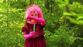 Een jonge heks in rituele kleren in een net bos voert rituele acties met zijn handen over een brandende kaars uit stock video