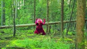 Een jonge heks in rood in een bosopen plek voert rituele acties met een personeel uit stock video