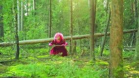 Een jonge heks in rood in het bos voert rituele acties met een personeel uit stock footage