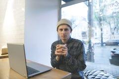 Een jonge hiphopmens zit in een comfortabele koffie dichtbij laptop en verwarmt omhoog koffie De freelancerwerken in een koffie w Royalty-vrije Stock Foto