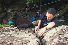 Een jonge hipster is bezig geweest met bergbeklimming met verzekering op rotsen met groen mos Stock Afbeelding