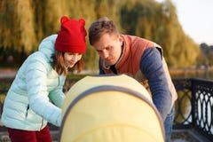 Een jonge houdende van familie loopt door het meer met een wandelwagen Het glimlachende ouderspaar met babykinderwagen in de herf Stock Afbeeldingen