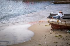 Een jonge jongen die in een boot leggen die in diepe gedachte schijnen te zijn royalty-vrije stock afbeelding