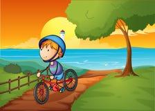 Een jonge jongen die dichtbij de rivier biking royalty-vrije illustratie