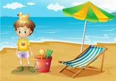 Een jonge jongen en zijn speelgoed bij het strand Stock Afbeelding