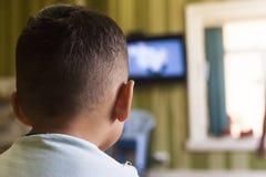 Een jonge jongen let op het televisiescherm met zijn rug voor een TVeffect op kinderen of een communicatie concept stock foto