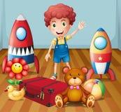 Een jonge jongen met zijn speelgoed binnen de ruimte Stock Foto