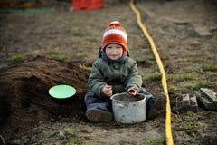 Een jonge jongen probeert om zijn ouders te helpen Stock Afbeelding