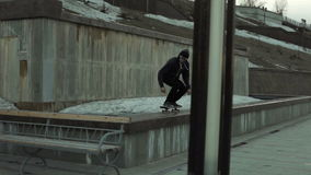 Een jonge jongen voert een truc op een skateboard uit stock video