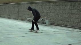 Een jonge jongen voert een truc op een skateboard uit stock videobeelden