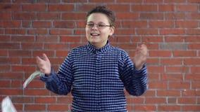 Een jonge jongen werpt geld met zijn handen stock video