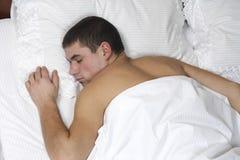 Een jonge jongensslaap in bed Stock Afbeelding