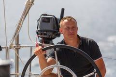 Een jonge kapitein bij het roer van een varend schip Sport royalty-vrije stock foto
