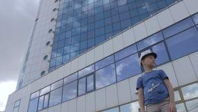 Een jonge kapitein dichtbij een lang hotel met een bezinning van de wolken stock video