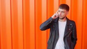 Een jonge Kaukasische kerel met een baard en een peinzend gezicht bevindt zich en denkt, oranje achtergrond, exemplaarruimte, lan stock videobeelden