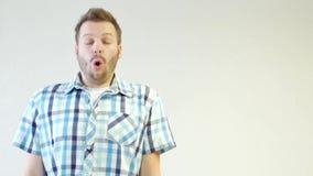 Een jonge Kaukasische mens met een baard ervaart emoties van vrees en verrassing, close-up, witte achtergrond, exemplaarruimte stock footage