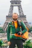 Een jonge Kaukasische Kaukasische mens met een oranje rugzak en een fotocamera in zijn handen bevindt zich in Frankrijk, Parijs t stock afbeeldingen