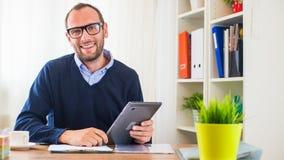 Een jonge Kaukasische mens met tablet in zijn bureau. Royalty-vrije Stock Foto's