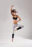 Een jonge Kaukasische vrouwelijke danser die in een sprong wordt gevangen royalty-vrije stock foto