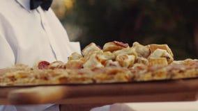 Een jonge kelner in het restaurant dienende banket, levert heerlijke Italiaanse schotels op een grote houten plaat, in langzaam stock videobeelden