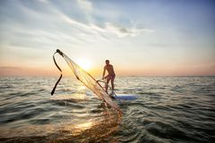 Een jonge kerel, een atleet heft een zeil op een windsurf op royalty-vrije stock afbeeldingen