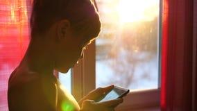 Een jonge kerel bevindt zich dichtbij een venster met een telefoon in zijn handen De zonsondergangtijd, de zon` s stralen gaat in stock video