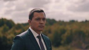 Een jonge kerel bevindt zich op de achtergrond van het bos en onderzoekt de afstand Knappe kerel Mooi Landschap Ernstig kijk stock video