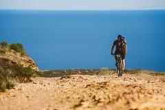 Een jonge kerel die een bergfiets berijden op een fietsroute in Spanje op weg tegen de achtergrond van de Middellandse Zee Royalty-vrije Stock Fotografie