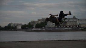 Een jonge kerel doet een salto mortale stock video