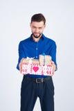 Een jonge kerel in een blauw overhemd met giften Stock Foto's